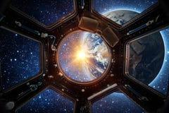 La terre et galaxie dans la fenêtre de Station Spatiale Internationale de vaisseau spatial image stock