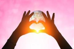 La terre et mains sous une silhouette en forme de coeur Photographie stock
