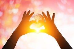 La terre et mains sous une silhouette en forme de coeur Photos libres de droits