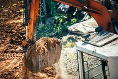 La terre mobile d'excavatrice sur le chantier de construction Plan rapproché de seau complètement de la terre Image libre de droits