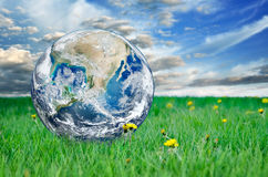 La terre parmi l'herbe verte contre le ciel bleu Éléments de cette image meublés par la NASA Photos stock