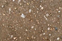La terre sous l'asphalte avec des pierres Image libre de droits