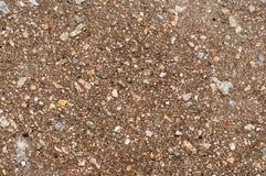 La terre sous l'asphalte avec des pierres davantage Photo stock