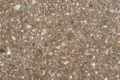 La terre sous l'asphalte avec des pierres plus aussi Photo libre de droits