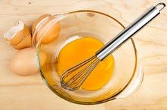 La terrina di vetro con i rossi d'uovo ed il metallo sbattono Fotografia Stock