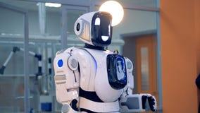 La testa del ` s del robot sta ottenendo ancora girata e posteriore con la sua mano che è di sollevamento video d archivio