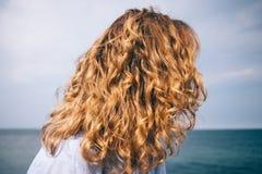 La testa della femmina posteriore di vista sul fondo blu del mare immagini stock libere da diritti
