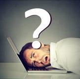 La testa di riposo sollecitata dell'uomo sul computer portatile sotto pressione dei problemi ha domande fotografia stock