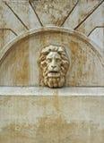 La testa di un leone sulla parete di vecchia fontana Fotografie Stock Libere da Diritti