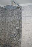 La testa e la ferrovia di doccia di massaggio di Chrome sul quadrato grigio piastrella il fondo fotografia stock