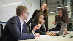 La testa ed il personale confrontano le idee davanti al computer portatile nell'auditorium stock footage