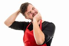 La testa maschio della tenuta del datore di lavoro del supermercato gradisce allungare il suo collo Fotografia Stock