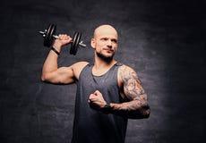 La testa rasa sportiva ha tatuato l'allenamento facente maschio della spalla con la testa di legno Immagine Stock Libera da Diritti