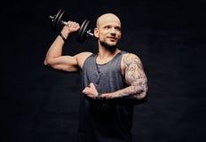 La testa rasa sportiva ha tatuato l'allenamento facente maschio della spalla con la testa di legno Immagine Stock