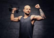 La testa rasa sportiva ha tatuato l'allenamento facente maschio della spalla con la testa di legno Immagini Stock Libere da Diritti