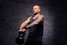 La testa rasa sportiva ha tatuato l'allenamento facente maschio della spalla con il Kettlebell Immagini Stock
