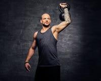 La testa rasa sportiva ha tatuato l'allenamento facente maschio della spalla con il Kettlebell Immagini Stock Libere da Diritti