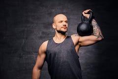 La testa rasa sportiva ha tatuato l'allenamento facente maschio della spalla con il Kettlebell Fotografia Stock