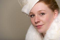 La testarossa che sorride nel bianco ha messo le piume al cappello ed alla pelliccia Fotografie Stock
