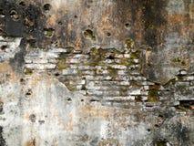 La textura de la pared del ladrillo del Grunge con el musgo rinde y los agujeros de bala fotografía de archivo libre de regalías