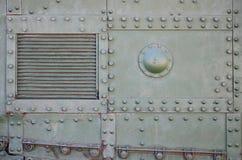 La textura de la pared del tanque, hecha del metal y reforzada con una multitud de pernos y de remaches Imágenes de la cubierta d fotografía de archivo