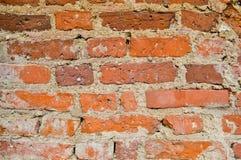 La textura de la piedra robusta antigua medieval antigua vieja que pela la pared rasguñada del ladrillo brillante anaranjado rojo imagen de archivo libre de regalías