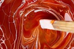 La textura de la pintura en los tonos rojo-anaranjados blancos, que se mezcla con un palillo fotografía de archivo libre de regalías