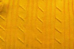 La texture d'un tissu de laine tricoté Fond pour créer des dispositions d'un hiver, cartes de Noël, bannières Chandail jaune de K Images stock