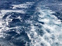 La texture de l'eau salée bleue agitée de mer avec des vagues, flaques, bulles, mousse, trace après un chariot de flottement rapi photos stock