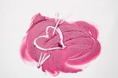 La texture du coeur dessiné par rouge à lèvres rose percé par une flèche, amour, trichant, maquillage Photos stock