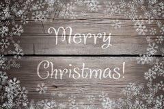 La texture en bois brune avec la neige et les étoiles blanches Fond de Noël Images stock