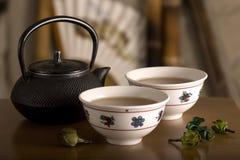 La théière chinoise, deux cuvettes et fruit sur la table. image libre de droits