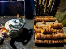 La théière et la bouilloire de terre dans un thé indien de bord de la route font des emplettes près du brûleur à charbon de combu photo libre de droits