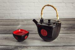 La théière et la place noires mettent en forme de tasse complètement du thé chaud avec la vapeur, avec le rouge Photo stock