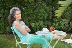 La théière se reposante de sourire de jardin de femme mûre mettent en forme de tasse le livre sur la table Photo stock