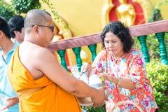 La Thaïlande 13 avril : : donnez l'aumône à un moine bouddhiste dans le Fest de Songkran images libres de droits