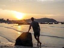 La Thaïlande - un garçon se penchant sur la roche image libre de droits