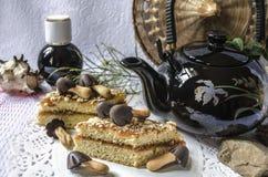 La théière avec des tranches de chocolat d'anf de gâteau répand Photo libre de droits