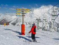 Skier looking at signpost in the ski resort of La Thuile, pointing towards different pistes including to the French resort of La R. La Thuile, Italy - Feb 18 Royalty Free Stock Image
