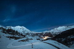 La Thuile ski resort at night. Aerial view of La Thuile village glowing in the night, famous ski resort in Aosta Valley, Italy. wonderful starry sky and majestic Royalty Free Stock Image