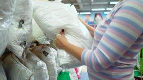 La tienda cercana de la mujer caucásica deja de lado elegir la almohada en tienda metrajes