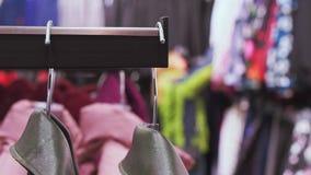 La tienda de ropa, mira a través de la ropa, mujer elige la ropa, ella está desenfocado almacen de metraje de vídeo