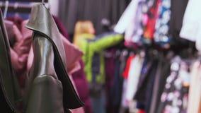 La tienda de ropa, mira a través de la ropa, mujer elige la ropa, ella está desenfocado almacen de video