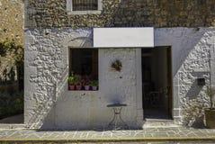 La tienda en blanco firma adentro el pequeño pueblo hermoso en Peloponesse imágenes de archivo libres de regalías
