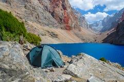 La tienda sola se coloca en la orilla de un lago hermoso de la montaña Imagenes de archivo