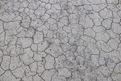 La tierra agrietada, secada es gris Un desierto sin el agua Tierra árida Sed para la humedad en un espacio sin vida Situati ecoló Fotos de archivo