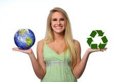 La tierra de la explotación agrícola de la mujer joven y recicla insignia Imagen de archivo libre de regalías