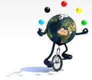 La tierra hace juegos malabares con los brazos y las piernas montan un unicycle Foto de archivo libre de regalías