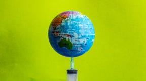 La tierra modelo en la jeringuilla con el fondo verde - imagen imagen de archivo libre de regalías