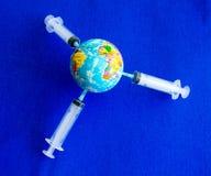 La tierra modelo en la jeringuilla en imagen de fondo azul fotos de archivo libres de regalías